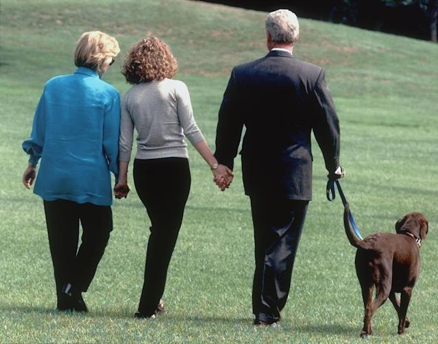 Hillary, Chelsea, and President Bill Clinton walk with Buddy in August 1998 as they leave the White House for vacation. (Photo: Roberto Borea/AP)