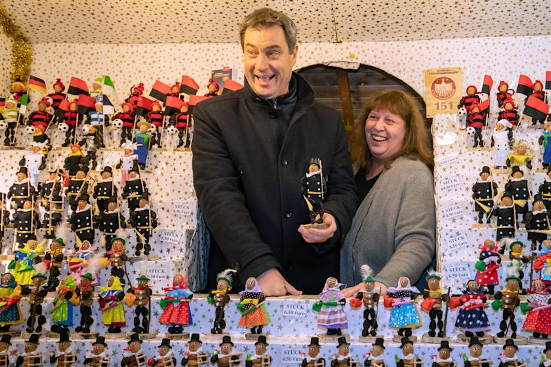 17 December 2019, Bavaria, Nuremberg: Markus Söder (CSU), Prime Minister of Bavaria, stands with a plum man in his hand after the cabinet meeting during a tour of the Nuremberg Christmas Market in the stand of Helga Scheller. The Council of Ministers of the Free State of Bavaria had previously met for its last working session in 2019. Photo: Daniel Karmann/dpa (Photo by Daniel Karmann/picture alliance via Getty Images)
