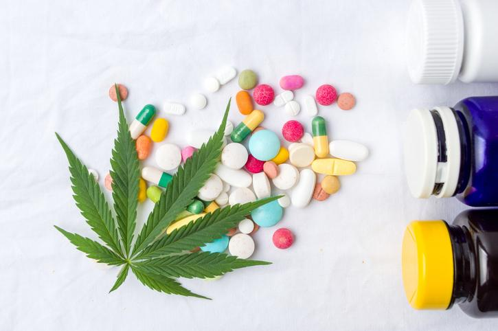 Overhead view of various types of pills lying on a surface with a marijuana leaf over them and three pill bottles lying on their sides adjacent to the pills.