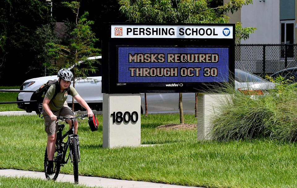 A boy rides his bicycle past a sign at Pershing School in Orlando, Fla., advising that face masks are required for students through Oct. 30, 2021.
