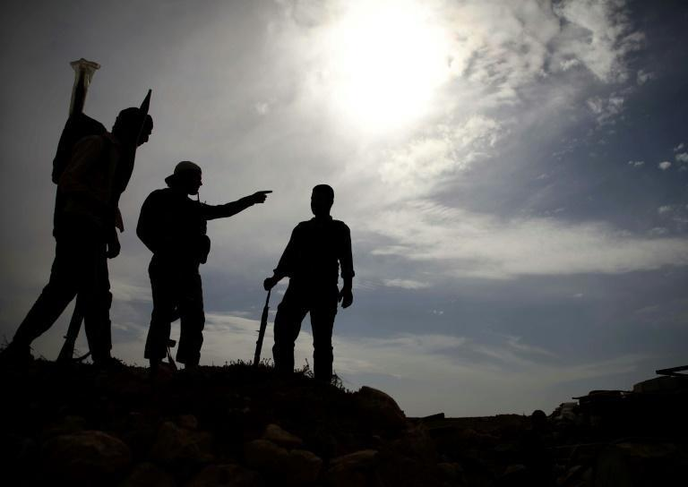 Syrian rebel-fighters with the National Liberation Front (NLF) stand on a hill overlooking regime-held areas in the northwestern countryside of Aleppo province on October 9, 2018