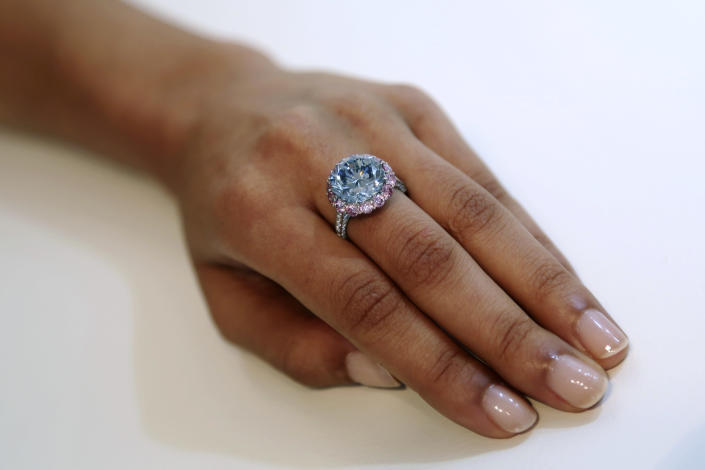 Sotheby's employee models a 7.59-carat internally flawless blue diamond at their New York auction house, Wednesday, Sept. 4, 2013 in New York. Sotheby's also had on display a 118-carat white diamond that will be auctioned in Hong Kong on Oct. 7 and has a pre-sale estimate of $28 million to $35 million. (AP Photo/Mary Altaffe)