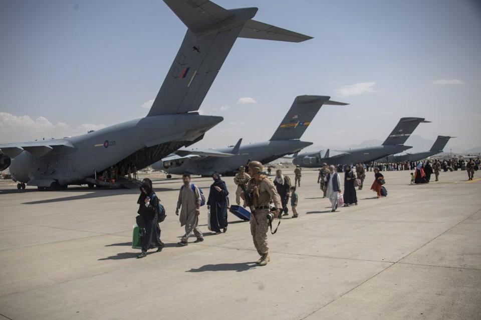 Members of the UK Armed Forces leading evacuees past a Royal Air Force Boeing C-17A Globemaster III at Kabul airport. (LPhot Ben Shread/MoD/PA) (PA Media)