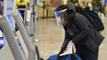 A traveler checks in before boarding a flight at Cleveland Hopkins International Airport, Wednesday, Nov. 25, 2020, in Cleveland. (AP Photo/Tony Dejak)