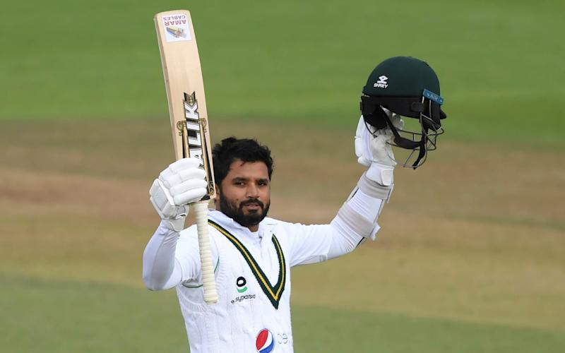 Pakistan's captain Azhar Ali raises his bat and helmet to celebrate scoring a century during the third day of the third cricket Test match between England and Pakistan, at the Ageas Bowl in Southampton, England, Sunday, Aug. 23, 2020. - AP