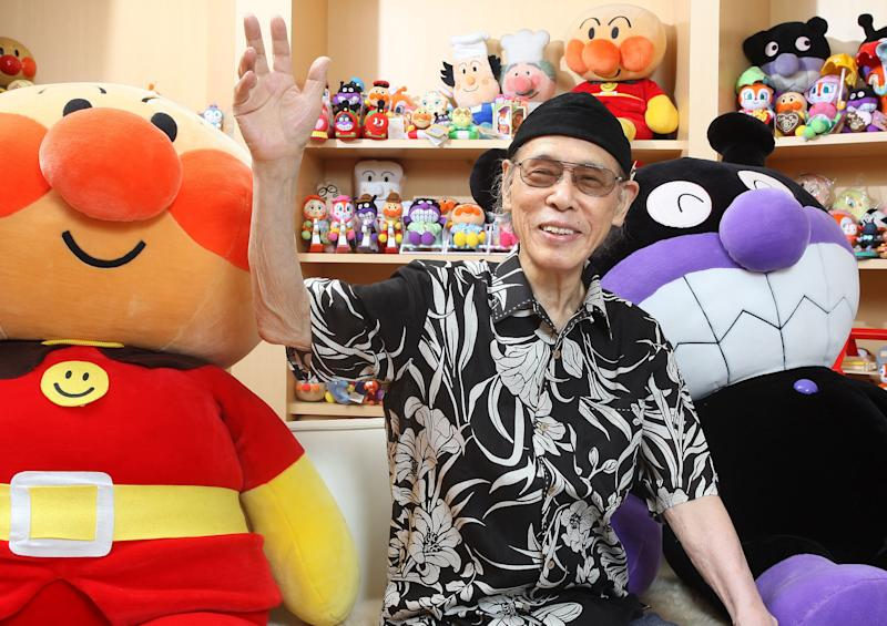 In this Aug. 2011 photo, Takashi Yanase, creator of one of Japan's most beloved cartoon characters, Anpanman, waves accompanied by Anpanman, left, and Baikinman at his Yanase Studio in Tokyo. His studio said Tuesday, Oct. 15, 2013 that Yanase died of heart failure at a Tokyo hospital early Sunday, Oct. 13. He had been treated for liver cancer since August. He was 94. (AP Photo/Kyodo News) JAPAN OUT, MANDATORY CREDIT