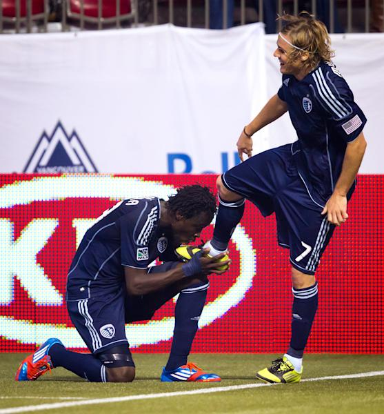Sporting Kansas City's Kei Kamara, left, of Sierra Leone, kisses the boot of teammate Chance Myers after Kamara scored a goal against the Vancouver Whitecaps during the second half of an MLS soccer match in Vancouver, British Columbia, Wednesday April 18, 2012. (AP Photo/The Canadian Press, Darryl Dyck)