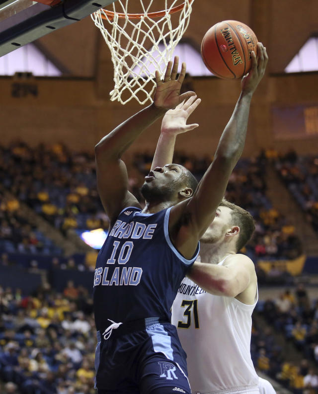 Rhode Island forward Cyril Langevine (10) goes to make a shot as he is defended by West Virginia forward Logan Routt (31) during the first half of an NCAA college basketball game Sunday, Dec. 1, 2019, in Morgantown, W.Va. (AP Photo/Kathleen Batten)