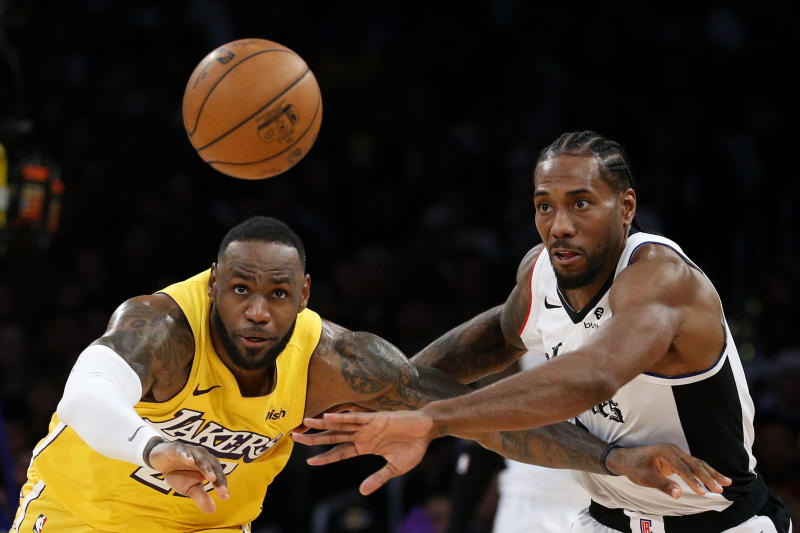 Los Angeles Lakers' LeBron James, left, and Los Angeles Clippers' Kawhi Leonard (2) chase the ball during the second half of an NBA basketball game Wednesday, Dec. 25, 2019, in Los Angeles. The Clippers won 111-106. (AP Photo/Ringo H.W. Chiu)