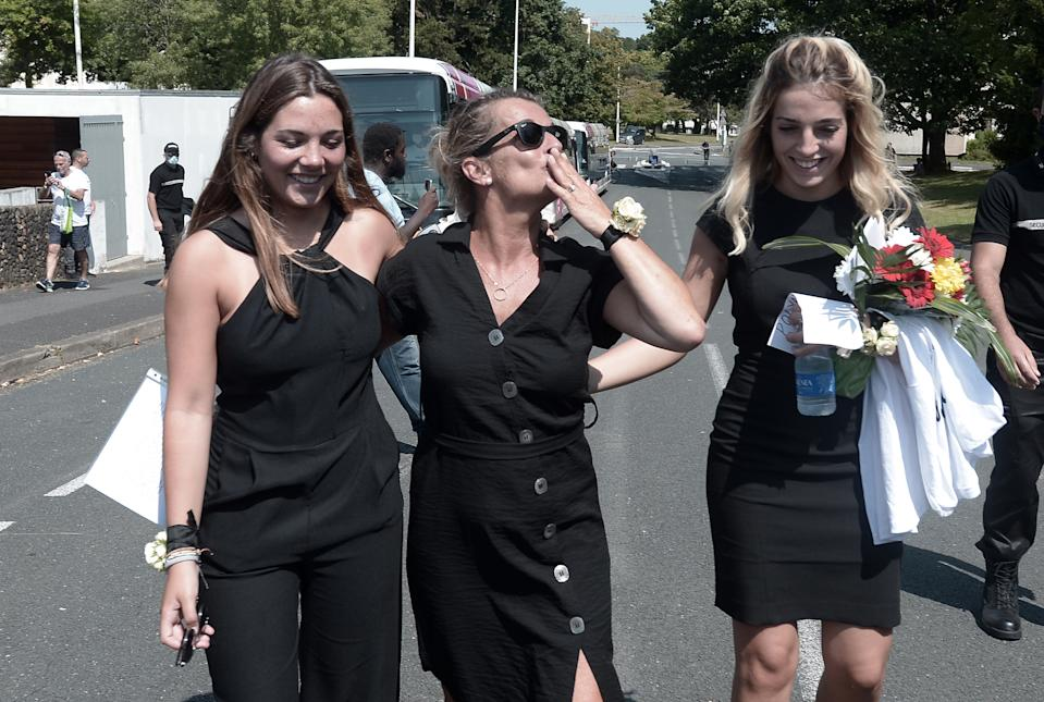 """Veronique Monguillot (C), the widow of French bus driver Philippe Monguillot who died after being beaten by passengers, waves to bus drivers flanked by her daughters Marie (L) and Manon (R), after her husband's funeral in Bayonne, southwestern France, on July 20, 2020. - French bus driver Philippe Monguillot, 59, was beaten by passengers on July 5 in Bayonne after asking them to wear face masks in line with coronavirus rules. He was left brain dead by the attack and died in hospital on July 11 after his family decided to switch off his life-support system. Two men have been charged with """"first-degree murder of a public transport official"""" and two others with """"non-assistance to a person in danger"""". (Photo by Iroz Gaizka / AFP) (Photo by IROZ GAIZKA/AFP via Getty Images)"""