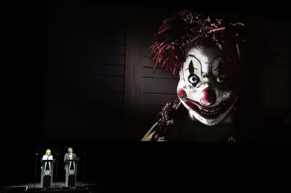 """Stacey Snider, left, co-chairman of 20th Century Fox, and Jim Gianopulos, chairman and CEO of 20th Century Fox, address the audience beneath an image from the upcoming film """"Poltergeist"""" during the 20th Century Fox presentation at CinemaCon 2015 at Caesars Palace on Thursday, April 23, 2015, in Las Vegas. (Photo by Chris Pizzello/Invision/AP)"""