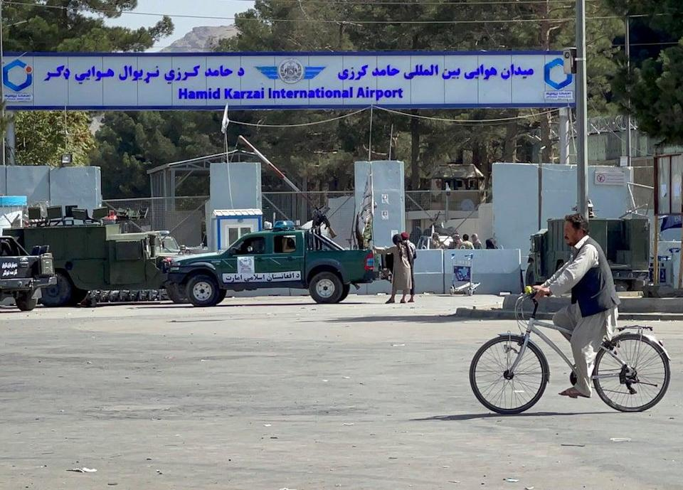 Taliban stand at the entrance gate of Hamid Karzai International airport on Friday (REUTERS)