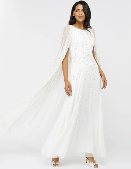"""<p><a class=""""link rapid-noclick-resp"""" href=""""https://go.redirectingat.com?id=127X1599956&url=https%3A%2F%2Fwww.monsoon.co.uk%2Fnaomi-embellished-cape-bridal-gown-ivory-84014046.html&sref=https%3A%2F%2Fwww.prima.co.uk%2Ffashion-and-beauty%2Ffashion-tips%2Fg34510%2Fwedding-dresses-under-500-pounds%2F"""" rel=""""nofollow noopener"""" target=""""_blank"""" data-ylk=""""slk:SHOP NOW"""">SHOP NOW</a></p><p>Sequinned, embellished and featuring an ankle-length cape, this is the design to make a statement in. </p><p>Naomi Embellished Cape Bridal Gown Ivory, £499, <a href=""""https://www.monsoon.co.uk/naomi-embellished-cape-bridal-gown-ivory-84014046.html"""" rel=""""nofollow noopener"""" target=""""_blank"""" data-ylk=""""slk:Monsoon"""" class=""""link rapid-noclick-resp"""">Monsoon</a></p>"""