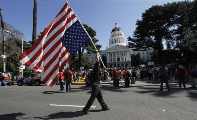 A protester carries an upside-down American flag during the Occupy the Capitol protest at the state Capitol in Sacramento, California March 5, 2012.