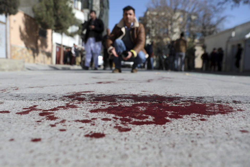 An Afghan journalist films the site where gunmen fired in Kabul, Afghanistan, Sunday, Jan. 17, 2021. Gunmen fired on a car in northern Kabul on Sunday, killing two women judges who worked for Afghanistan's high court and wounding the driver, a court official said. It was the latest attack in the Afghan capital during peace talks between Taliban and Afghan government officials in Qatar. (AP Photo/Rahmat Gul)