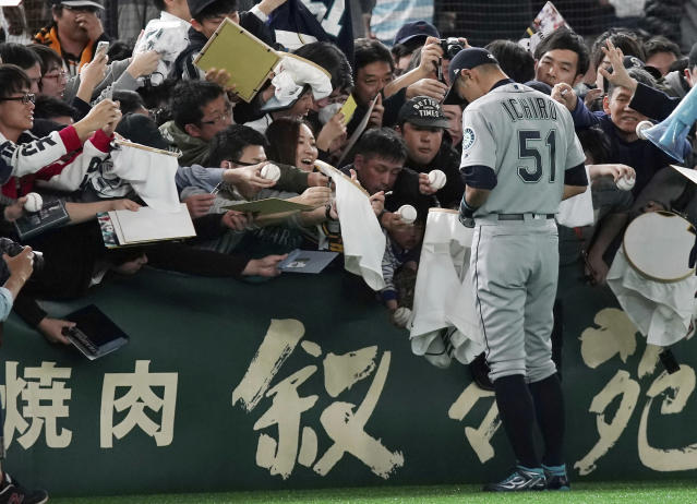 Seattle Mariners right fielder Ichiro Suzuki gives his autograph to fans prior to a pre-season exhibition baseball game between the Mariners and the Yomiuri Giants at Tokyo Dome in Tokyo Sunday March 17, 2019. (AP Photo/Eugene Hoshiko)