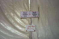 """Signs mark a clothes drop in a tent city for electrical workers in Amelia, La., Thursday, Sept. 16, 2021. When Hurricane Ida was brewing in the Gulf of Mexico, the grass was chest high and the warehouse empty at this lot in southeastern Louisiana. Within days, electric officials transformed it into a bustling """"tent city"""" with enormous, air-conditioned tents for workers, a gravel parking lot for bucket trucks and a station to resupply crews restoring power to the region. (AP Photo/Gerald Herbert)"""