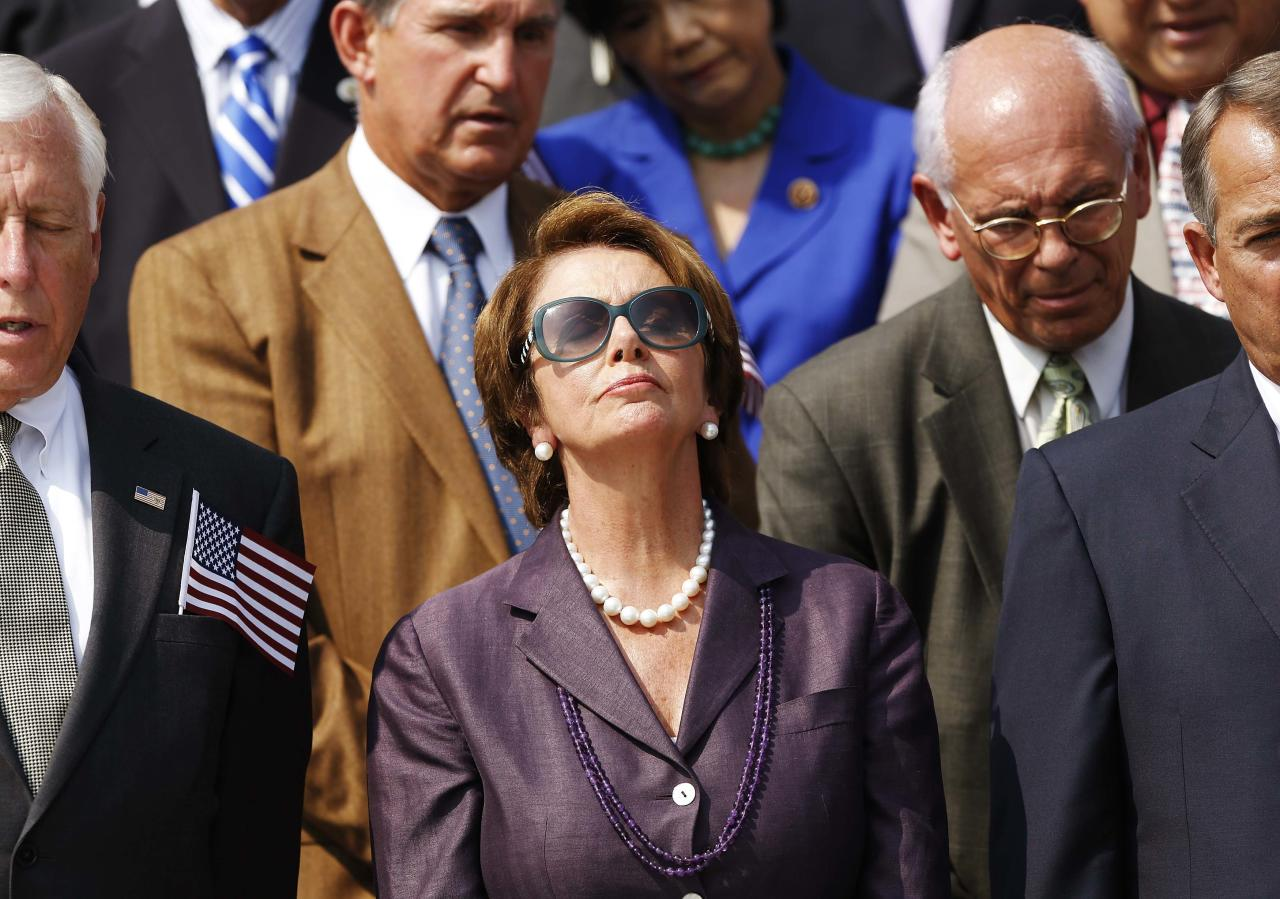U.S. House Minority Leader Nancy Pelosi (D-CA) (C) observes a moment of silence during a remembrance of lives lost in the 9/11 attacks, on the steps of the U.S. Capitol in Washington, September 11, 2013. Bagpipes, bells and a reading of the names of the nearly 3,000 people killed when hijacked jetliners crashed into the World Trade Center, the Pentagon and a Pennsylvania field marked the 12th anniversary of the September 11 attacks in 2001. REUTERS/Jonathan Ernst (UNITED STATES - Tags: POLITICS ANNIVERSARY DISASTER)