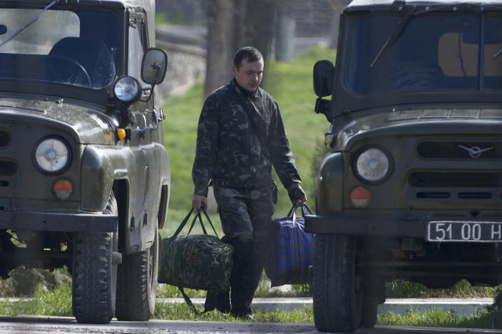 A Ukrainian air force officer carries his bags at the Belbek airbase, outside Sevastopol, Crimea, on Thursday, March 20, 2014. With thousands of Ukrainian soldiers and sailors trapped on military bases, surrounded by heavily armed Russian forces and pro-Russia militia, the Kiev government said it was drawing up plans to evacuate its outnumbered troops from Crimea back to the mainland and would seek U.N. support to turn the peninsula into a demilitarized zone. (AP Photo/Ivan Sekretarev)