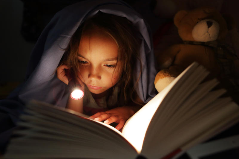 Girl under bed covers reading book by torchlight