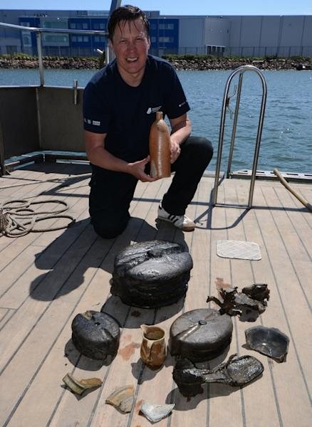 Tomasz Bednarz, an underwater archaeologist the National Maritime Museum, holds the 200-year-old Selters bottle with other shipwreck finds in front of him.