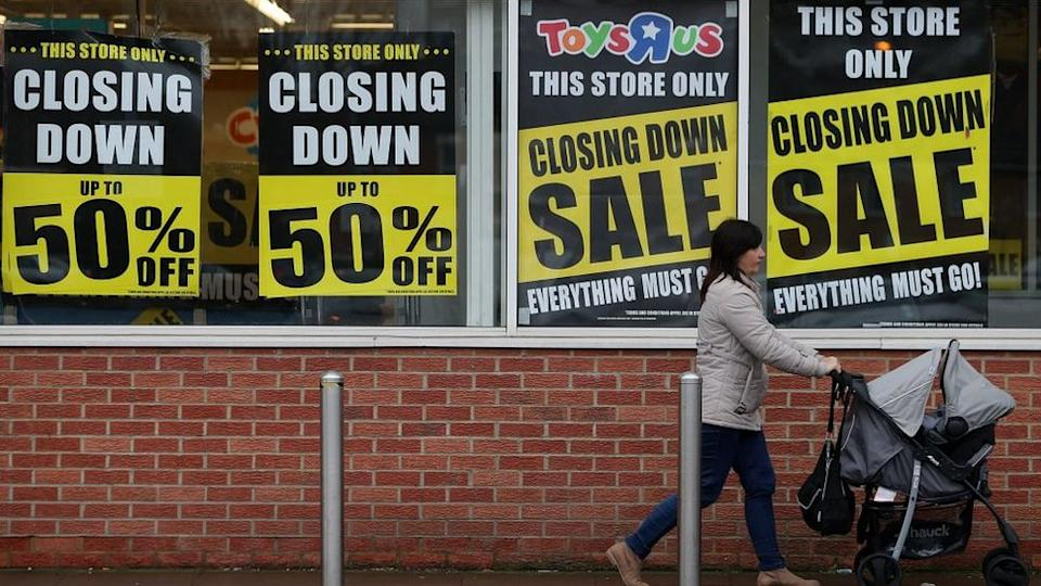 A customer walks past a Toys 'R' Us store with 'closing down sale' signs in the windows in south London on February 9, 2018
