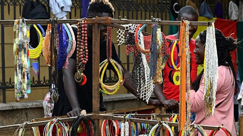 A visitor speaks to a man running a stall selling beaded necklaces displayed at the Maasai market in Nairobi on June 16, 2019