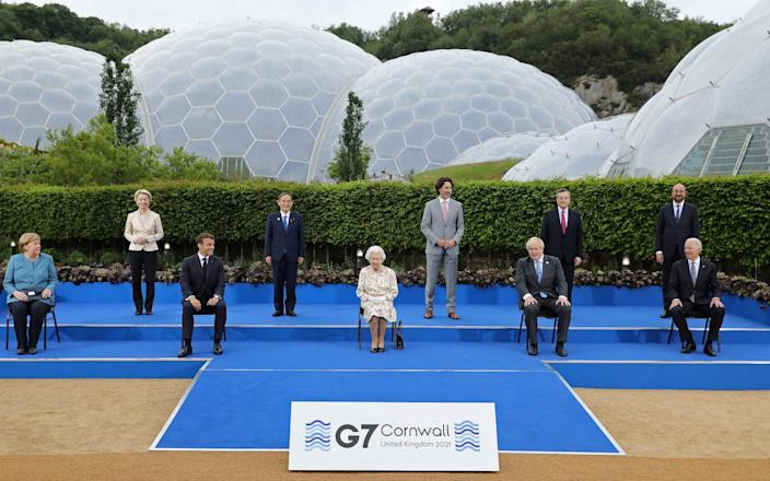 The Queen poses for a family photograph with G7 leaders, including Angela Merkel, Ursula von der Leyen, Emmanuel Macron, Yoshihide Suga, Justin Trudeau, Boris Johnson, Mario Draghi, Charles Michel and Joe Biden, in Cornwall, on June 11 2021. - Jack Hill/AFP