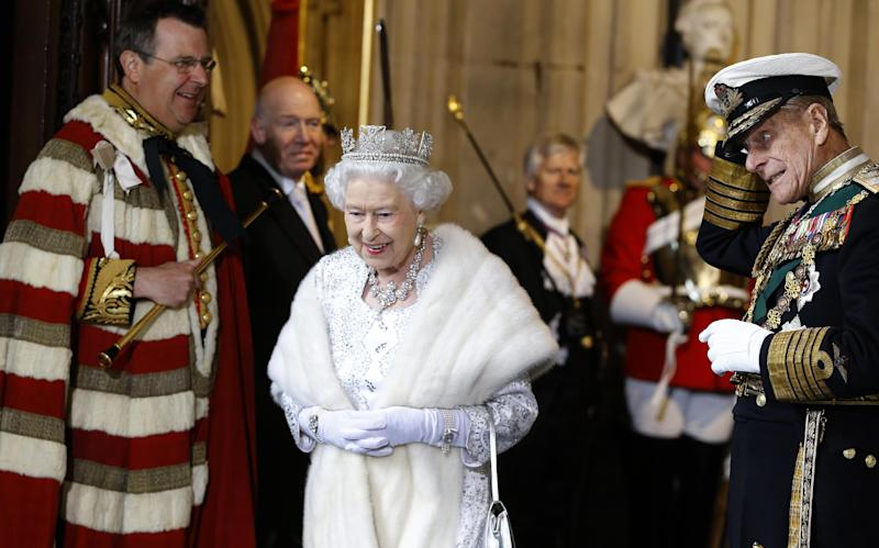 Britain's Queen Elizabeth II smiles with The Duke of Edinburgh, right, as they leave after the State Opening of Parliament, at the Houses of Parliament in London, Wednesday, May 8, 2013. The State Opening of Parliament marks the formal start of the parliamentary year, the Queen will deliver a speech which will set out the government's agenda for the coming year. (AP Photo/Kirsty Wigglesworth, Pool)
