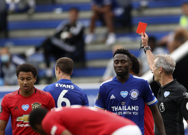 Referee Martin Atkinson, right, shows a red card to Leicester's Jonny Evans, second left, during the English Premier League soccer match between Leicester City and Manchester United at the King Power Stadium, in Leicester, England, Sunday, July 26, 2020. (Carl Recine/Pool via AP)