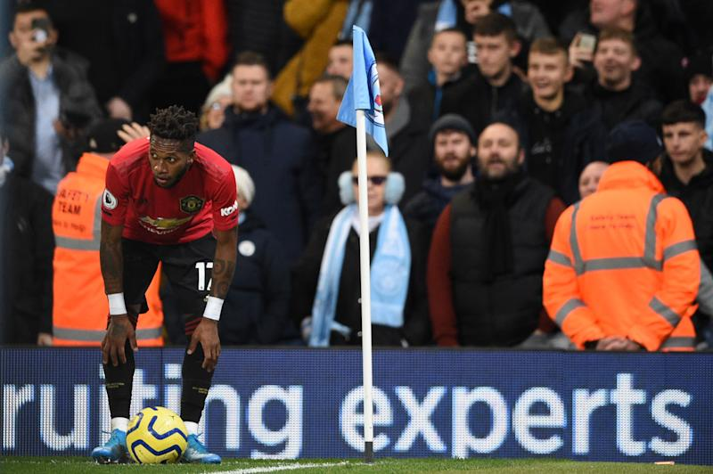 Manchester United's Brazilian midfielder Fred (L) tries to take a corner kick after being pelted with objects from the crowd during the English Premier League football match between Manchester City and Manchester United at the Etihad Stadium in Manchester, north west England, on December 7, 2019. - Fred was hit by objects thrown from the crowd as he prepared to take a corner in the second half while footage on social media appeared to show a City fan mimicking a monkey at the Brazilian. (Photo by Oli SCARFF / AFP) / RESTRICTED TO EDITORIAL USE. No use with unauthorized audio, video, data, fixture lists, club/league logos or 'live' services. Online in-match use limited to 120 images. An additional 40 images may be used in extra time. No video emulation. Social media in-match use limited to 120 images. An additional 40 images may be used in extra time. No use in betting publications, games or single club/league/player publications. / (Photo by OLI SCARFF/AFP via Getty Images)