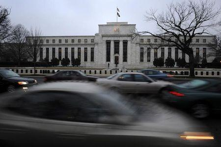 Morning commuters drive past the Federal Reserve Bank building in Washington