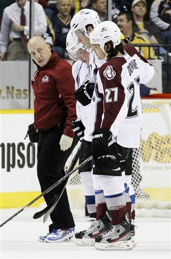 Colorado Avalanche defenseman Erik Johnson, second from right, is helped to the bench by Steve Downie (27) and Paul Stastny, second from left, in the first period of an NHL hockey game against the Nashville Predators on Thursday, March 8, 2012, in Nashville, Tenn. (AP Photo/Mark Humphrey)