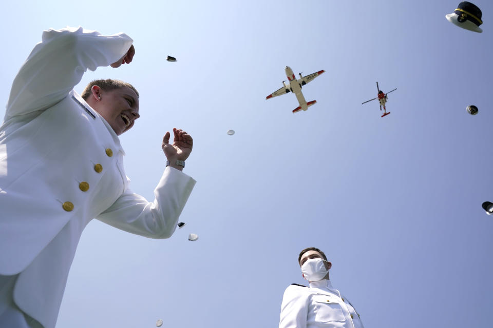 Ensign Charlee Kraiss, left, and Ensign Isaac Lalonde toss their hats in the air as planes fly over at the commencement for the United States Coast Guard Academy in New London, Conn., Wednesday, May 19, 2021. (AP Photo/Andrew Harnik)
