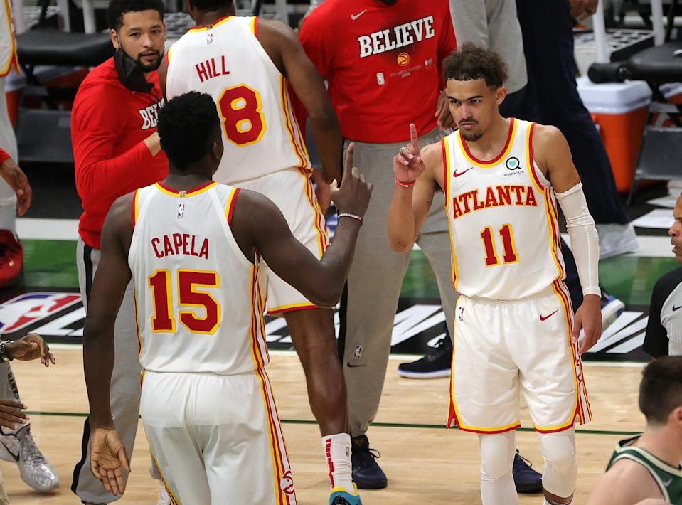 Trae Young and Clint Capela each hold up one finger to celebrate their Game 1 win.