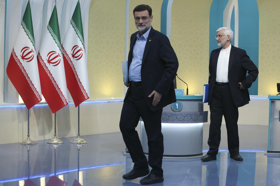 """In this picture made available by Young Journalists Club, YJC, presidential candidate for June 18, elections Amir Hossein Ghazizadeh Hashemi, left, and Saeed Jalili leave a studio of the state-run TV at the conclusion of a part of the final debate of the candidates, in Tehran, Iran, Saturday, June 12, 2021. Iran's seven presidential candidates offered starkly different views Saturday in the country's final debate, with hard-liners describing those seeking ties with the West as """"infiltrators"""" and the race's sole moderate warning a hard-line government would only bring more sanctions for the Islamic Republic. (Morteza Fakhri Nezhad/ Young Journalists Club, YJC via AP)"""