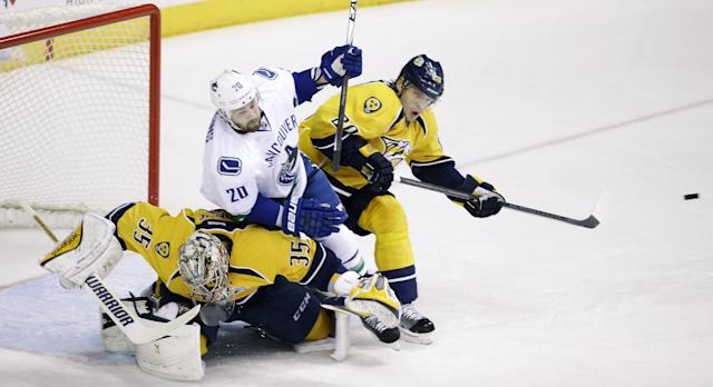 Vancouver Canucks left wing Chris Higgins (20) collides with Nashville Predators goalie Pekka Rinne (35), of Finland, and defenseman Anton Volchenkov (20), of Russia, in the first period of an NHL hockey game Tuesday, Jan. 13, 2015, in Nashville, Tenn. Higgins was called for goaltender interference. (AP Photo/Mark Humphrey)