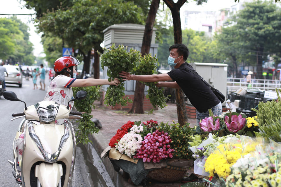 A seller hands flowers to a customer, both wearing face masks, in Hanoi, Vietnam, Monday, Aug. 3, 2020. Vietnam has tightened travel and social restrictions after the country's death toll of COVID-19 to six. (AP Photo/Hau Dinh)