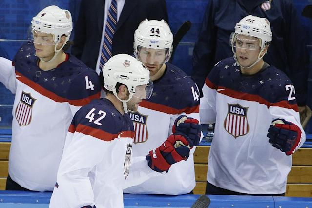 USA forward David Backes celerates his goal against Slovakia with his teammates on the bench during the 2014 Winter Olympics men's ice hockey game at Shayba Arena, Thursday, Feb. 13, 2014, in Sochi, Russia. (AP Photo/Matt Slocum)