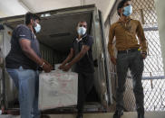A Sri Lankan health services workers unload a consignment of Oxford-AstraZeneca vaccine donated by the Indian government at a medical warehouse as a plain clothed police officer stands guard in Colombo, Sri Lanka, Thursday, Jan. 28, 2021. Sri Lanka's president on Thursday welcomed the first 500,000 doses of a COVID-19 vaccine from India, which has donated the shots to eight countries in the region. (AP Photo/Eranga Jayawardena)