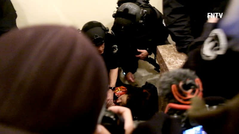 Police help a woman, who was shot, as she lies on the floor, after supporters of U.S. President Donald Trump entered the Capitol building in Washington DC, U.S. , in this still frame obtained from social media video