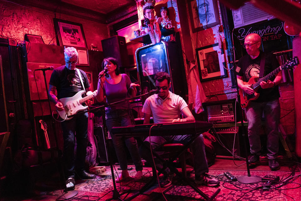 Elissa Montanti, founder and director at The Global Medical Relief Fund, second from left, performs with Ahmed Shareef, center right, at Liedy's Shore Inn, Tuesday, June 15, 2021 in the Staten Island borough of New York. Shareef and Montanti have become family after his arrival to the United States from Iraq for medical treatment through the charity. Through music and art, Montanti coped with the isolation of pandemic lockdowns waiting for the day she could reopen her charity and resume her life's work. (AP Photo/John Minchillo)