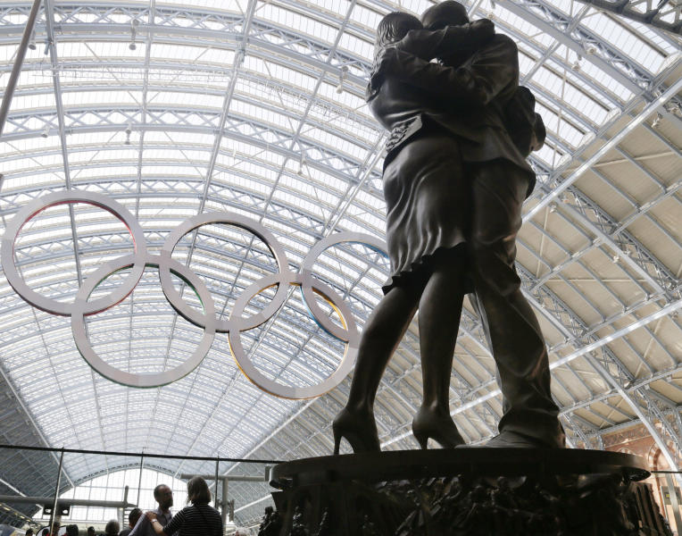 A couple pauses at the foot of a statue with the Olympic rings hung in the rafters of St. Pancras Station prior to the 2012 Summer Olympics, Tuesday, July 24, 2012, in London. The opening ceremonies for the 2012 London Olympics will be held Friday, July 27. (AP Photo/Charles Krupa)