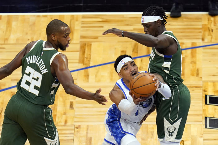 Orlando Magic guard Gary Harris, center, works to get between Milwaukee Bucks forward Khris Middleton (22) and guard Jrue Holiday during the first half of an NBA basketball game, Sunday, April 11, 2021, in Orlando, Fla. (AP Photo/John Raoux)