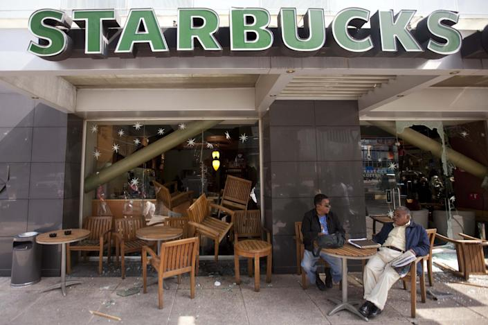 Two customers sit outside a Starbucks vandalized by angry protestors in opposition to Mexico's newly sworn-in president, in Mexico City, Saturday, Dec. 1, 2012. Protests began early Saturday morning with violent confrontations in the streets and protest speeches from opposition parties inside the congress, where Enrique Pena Nieto took the oath of office. Protesters continued vandalizing downtown businesses, smashing plate glass windows and setting office furniture ablaze outside. (AP Photo/Eduardo Verdugo)