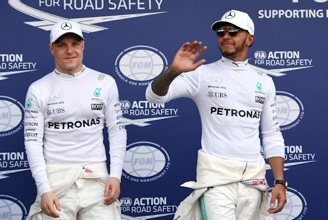 Mercedes' British driver Lewis Hamilton (R) and Finnish teammate Valtteri Bottas celebrate after the qualifying session at the Formula One Australian Grand Prix in Melbourne on March 25, 2017 (AFP Photo/William WEST)