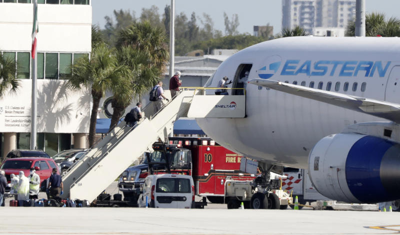 Passengers that came off the cruise ship Rotterdam Thursday, board a charter plane at Fort Lauderdale–Hollywood International Airport, Friday, April 3, 2020, in Fort Lauderdale, Fla.  The Zaandam and a sister ship sent to help it, the Rotterdam, were given permission to unload passengers at Port Everglades on Thursday, after days of negotiations with officials who feared it would divert resources from a region with a spike in virus cases. (AP Photo/Wilfredo Lee)