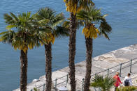 Tourists walk past palm trees in Opatija, Croatia, Saturday, May 15, 2021. Croatia has opened its stunning Adriatic coastline for foreign tourists after a year of depressing coronavirus lockdowns and restrictions. (AP Photo/Darko Bandic)