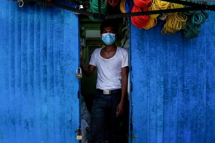 A man stands at the entrance to his shop in downtown Yangon, Myanmar (AFP Photo/Sai Aung Main)
