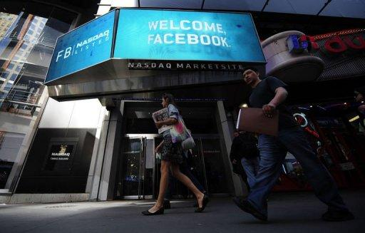 People walk past a sign welcoming Facebook at the NASDAQ stock exchange